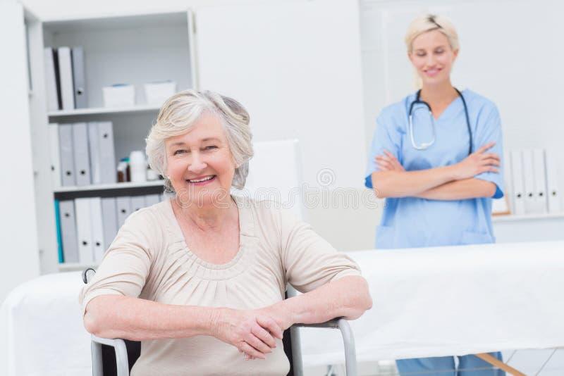 Seduta paziente senior sulla sedia a rotelle mentre infermiere che sta nel fondo immagini stock libere da diritti