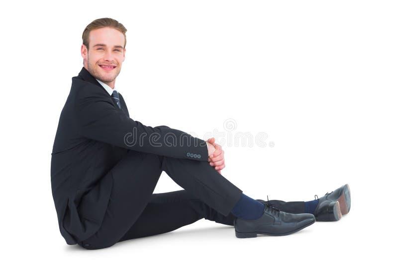 Seduta rilassata e sorridere dell'uomo d'affari immagine stock