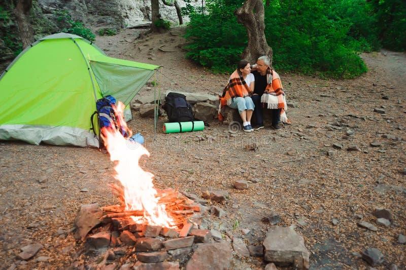 Seduta romantica di campeggio delle coppie della tenda dalla campagna di notte del falò fotografia stock