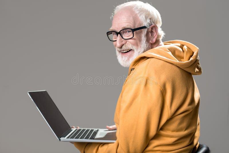 Seduta senior contenta davanti al taccuino immagine stock