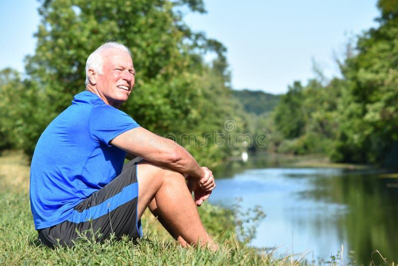 Seduta senior maschio atletica sorridente dal fiume immagini stock libere da diritti