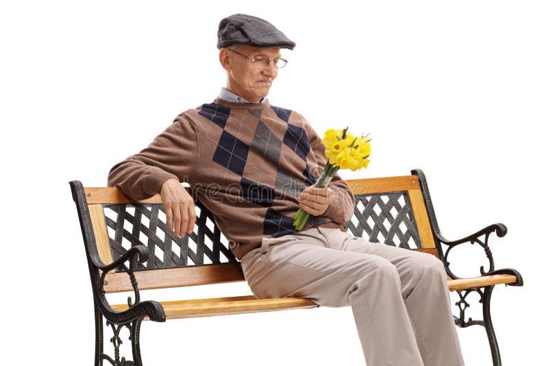 Seduta senior su stata su un banco fotografia stock