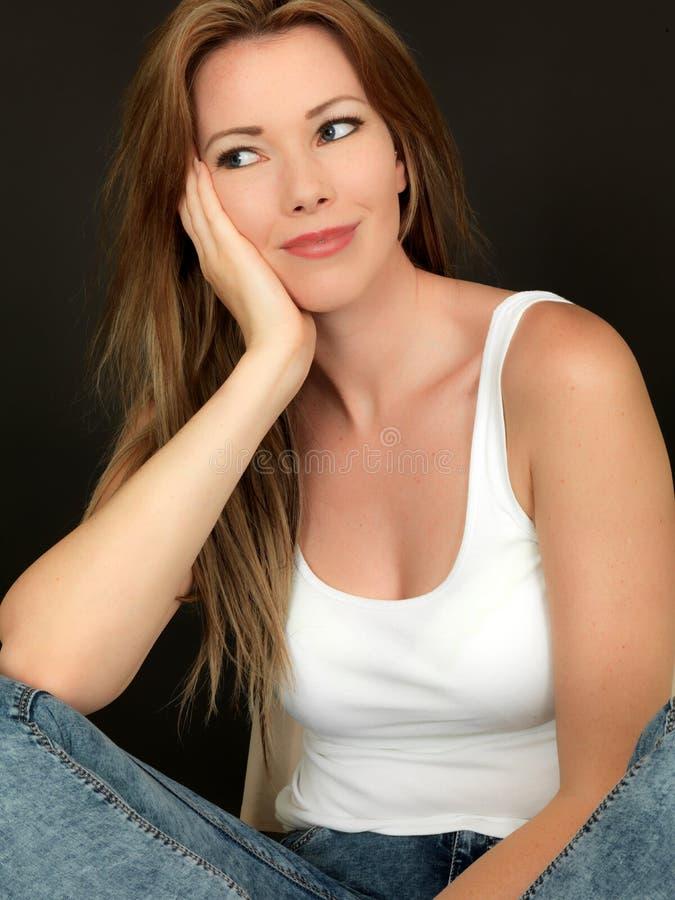Seduta sorridente della bella giovane donna rilassata felice in una sedia immagine stock libera da diritti