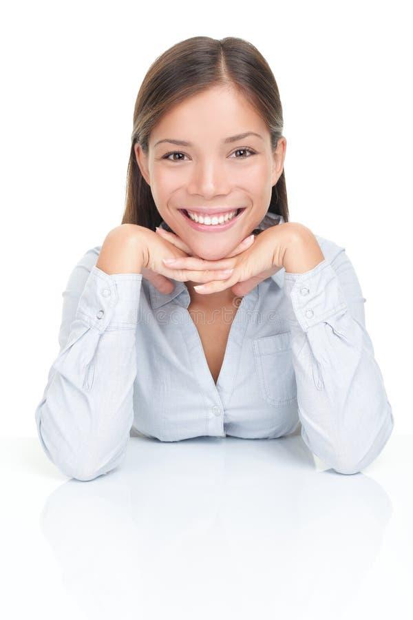 Seduta sorridente della giovane donna alla tabella fotografia stock