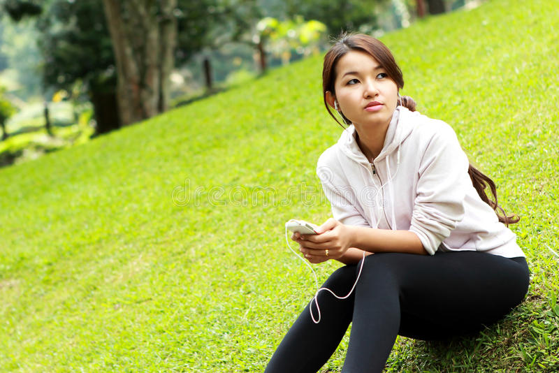 Seduta sportiva della donna mentre ascoltando una musica fotografia stock libera da diritti