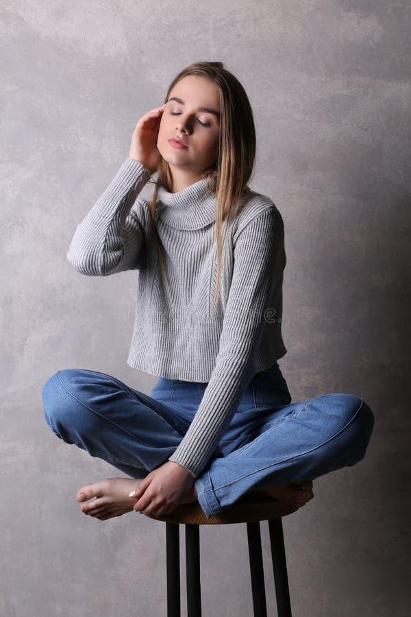 Seduta teenager in pullover che tocca il suo fronte Fondo grigio immagini stock libere da diritti