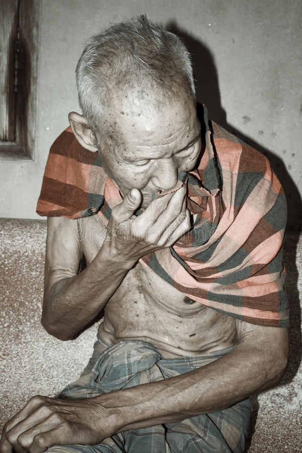 Seduta triste dell'uomo anziano da solo sulla sedia immagine stock