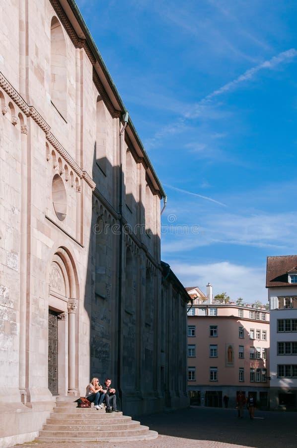 Seduta turistica ai punti di vecchia costruzione di chiesa medievale nella vecchia città Altstadt di Zurigo fotografie stock