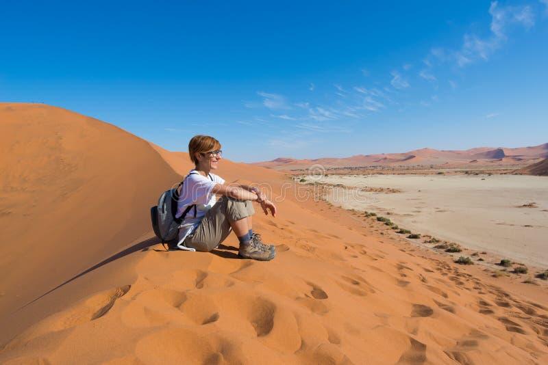 Seduta turistica rilassata sulle dune di sabbia ed esaminare la vista sbalorditiva in Sossusvlei, deserto di Namib, migliore dest immagine stock libera da diritti