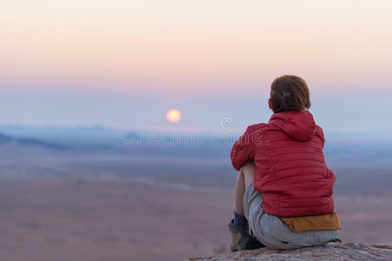 Seduta turistica rilassata sulle rocce ed esaminare il tramonto nel deserto di Namib, migliore destinazione di viaggio in Namibia fotografia stock