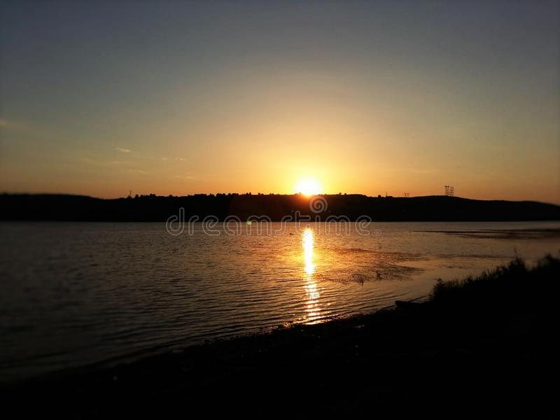 See auf einem ruhigen Ufer in einem glänzenden rasenden Himmel und in einer schönen Landschaft stockfotografie