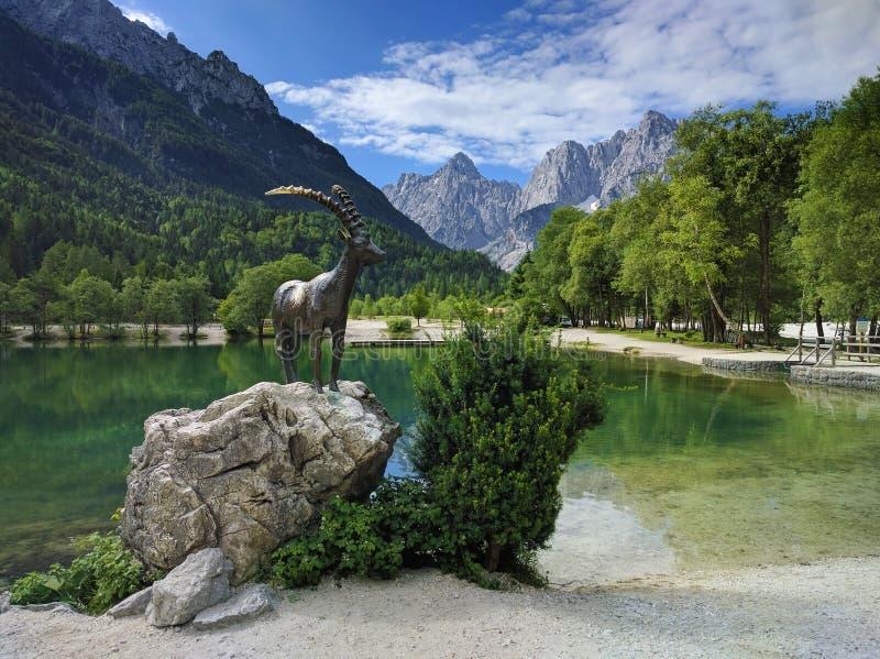 See Jasna und Gebirgsziegenstatue in Kranjska Gora, Slowenien lizenzfreies stockfoto