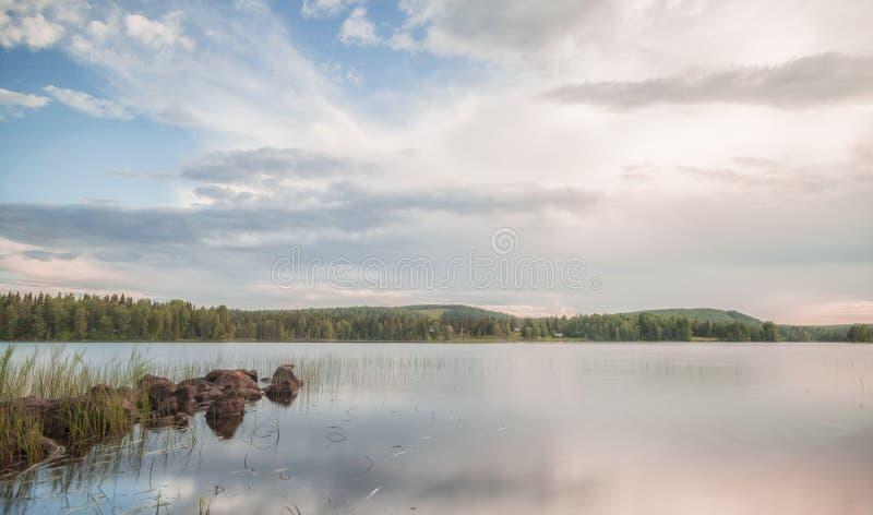 See mit Felsen und Wald stockbilder