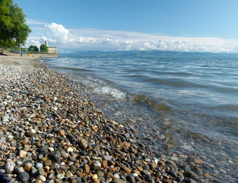 See mit Kiesstrand und Wasserschloss- und großenwolken im Hintergrund lizenzfreie stockfotografie