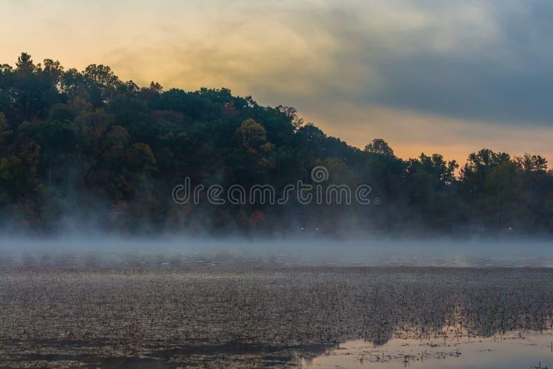 See mit Nebel am Morgen mit bunten Wolken im Himmel lizenzfreies stockfoto