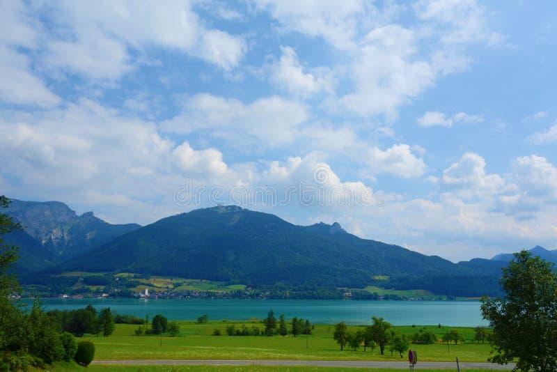 See nannte Wolfgangsee in Österreich mit Bergen im Hintergrund und Wolken auf dem Himmel und dem Gras in der Front lizenzfreie stockfotos