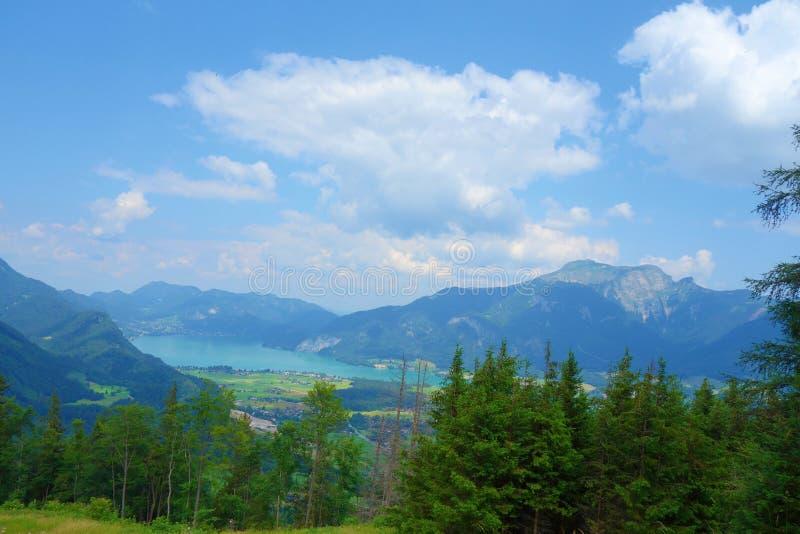 See nannte Wolfgangsee in Österreich mit Bergen im Hintergrund und Wolken auf dem Himmel und dem Gras in der Front stockbild