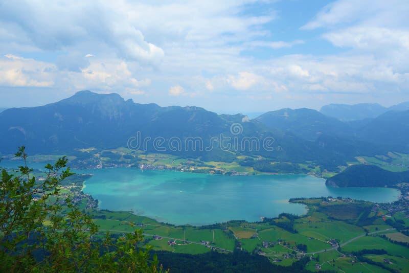 See nannte Wolfgangsee in Österreich mit Bergen im Hintergrund und Wolken auf dem Himmel und dem Gras in der Front stockbilder