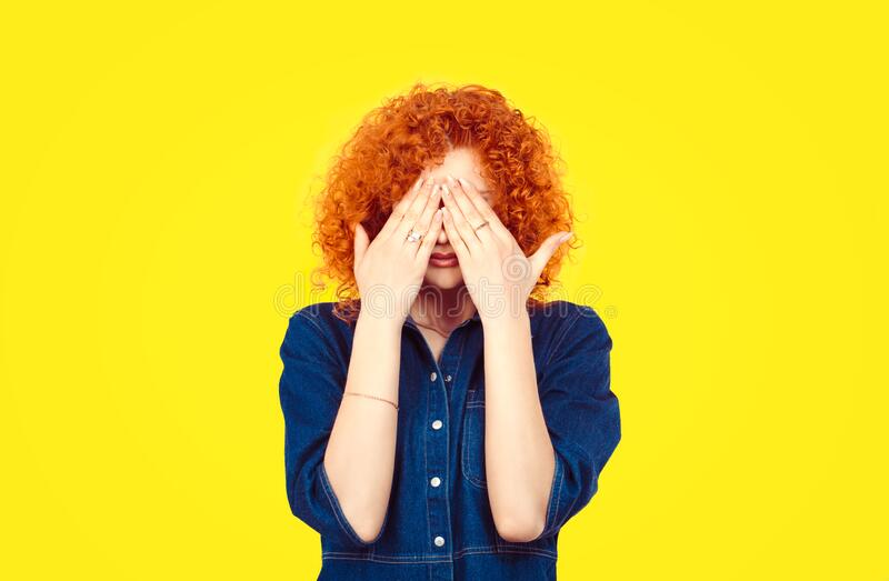 See no evil concept. Closeup portrait young redhead curly hair woman closing covering eyes with hands can`t look hiding avoiding. Situation isolated yellow royalty free stock images