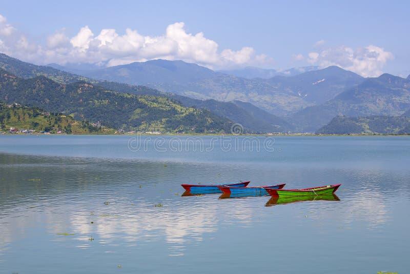 See Phewa, hölzernes Boot in Pokhara, Nepal, mit den Himalajabergen im Hintergrund stockfotografie
