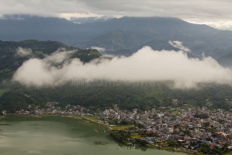 See Phewa und Häuser Pokhara, Nepal, mit den Himalajabergen im Hintergrund stockbilder