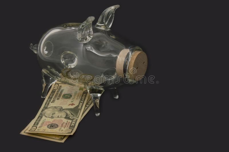 A see through piggy bank with money coins.Banknotes under the piggy bank stock photos