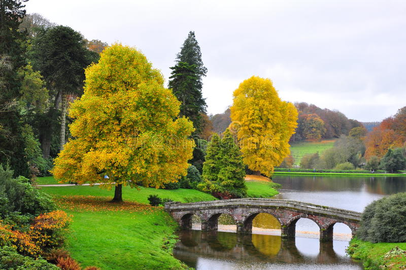 See und Brücke im Herbst - Stourhead-Garten stockbild