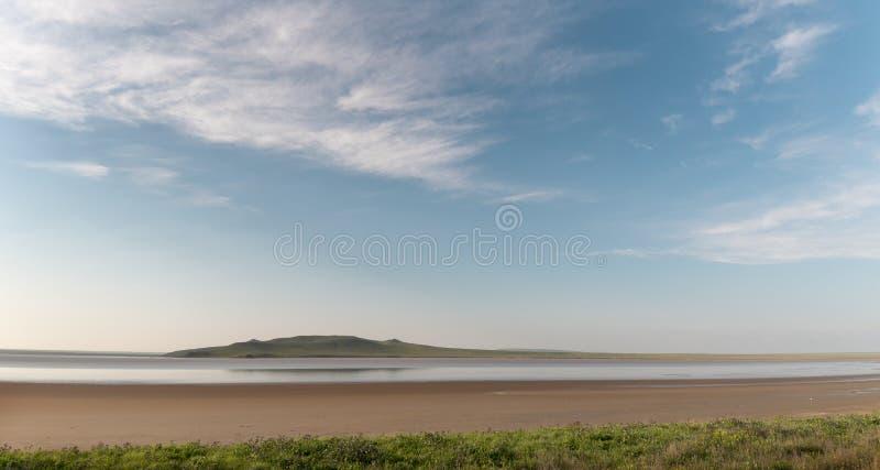 See und Hügel unter einem blauen Himmel mit Wolken lizenzfreies stockfoto