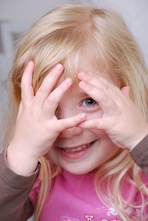 See You. A young girl playing peek-a-boo stock images