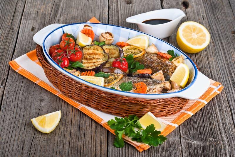 Seebarschfische backten mit Gemüse, Kräutern und Zitrone lizenzfreie stockfotografie