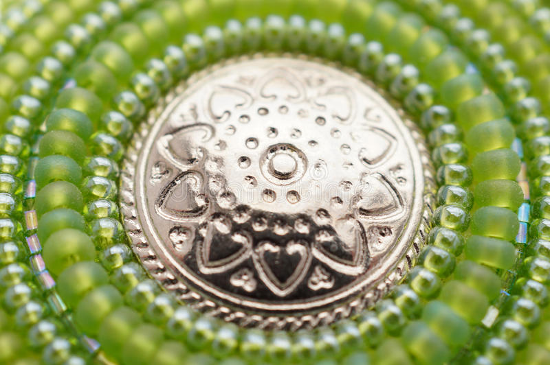 Seed bead embroidered green mandala with metal button. Hand made art object stock photography