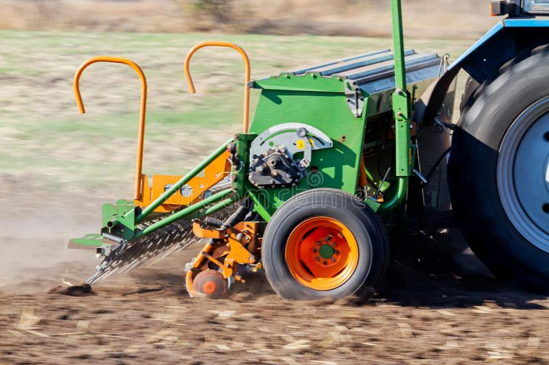 Seeder sows wheat in black soil. Exclusive stock photography
