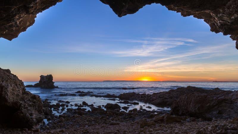 Seehöhle am Sonnenuntergang mit hellen Wolken und an den rosa und orange Farben über dem Pazifischen Ozean im Orange County, Kali lizenzfreies stockfoto