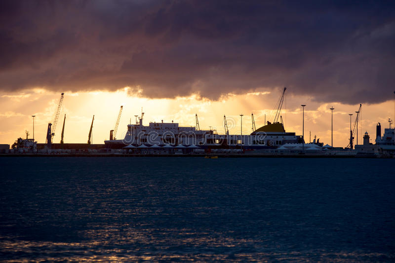 Seehafen mit großen Schiffen und Leuchtturm bei Sonnenuntergang stockbild