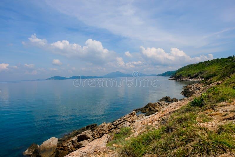 Seehorizont mit felsigen Uferklippen und hellblauem Himmelhintergrund der Sonne Meereswellen, die auf Felsen zusammenstoßen stockfotografie