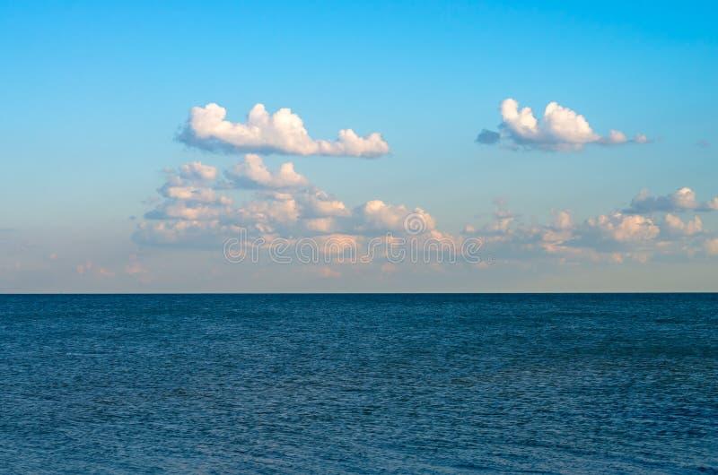 Seehorizont mit kleinen Wellen, blauer Himmel mit weißen Wolken lizenzfreies stockfoto
