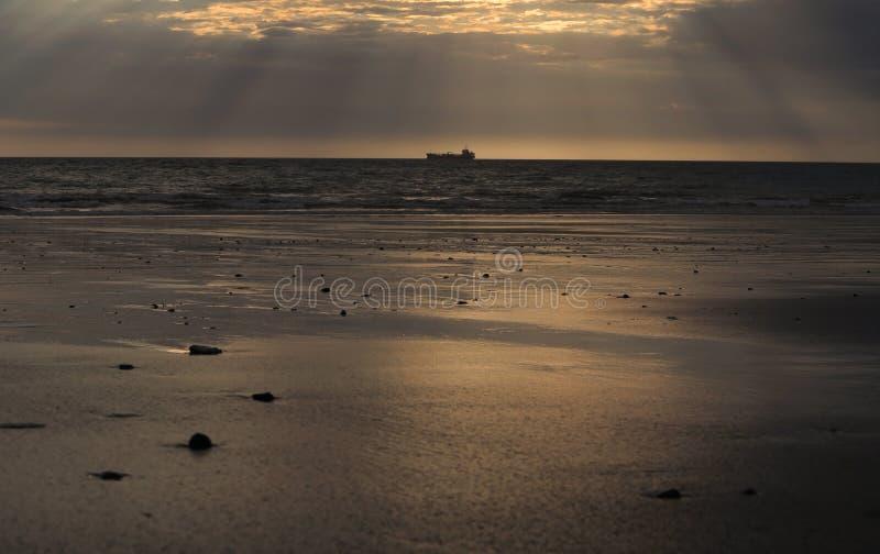 Seehorizont mit Schiffs-Schattenbild Morgen-Himmel reflektieren sich im nassen Strand-Sand stockfotos