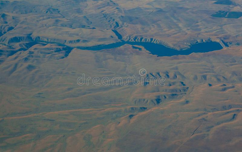 Seeing the californian landscape from above. Hanford, United States - October 14 2013 : The high desert. Mountains in the desert, shadows and an irrigation stock photography