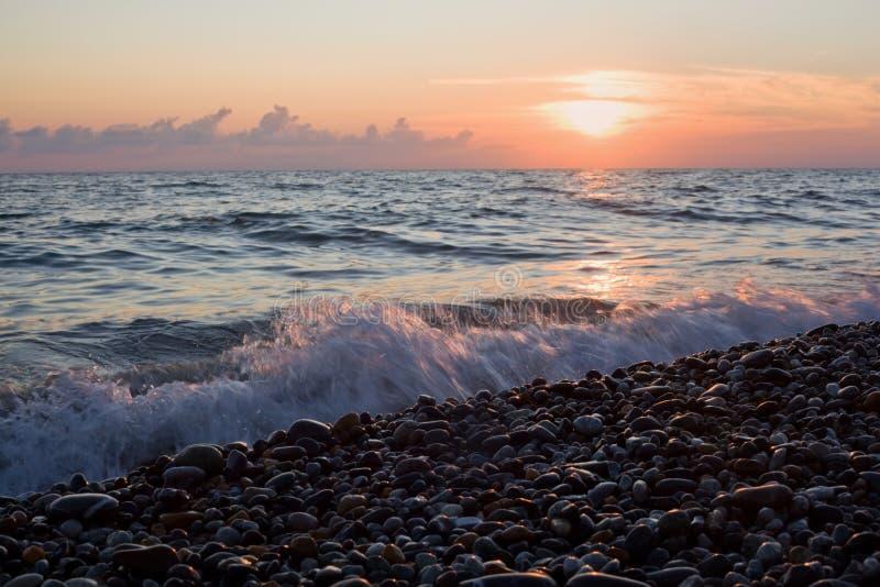 Seeküste mit Wellen auf Sonnenuntergang, steiniger Strand stockfotografie