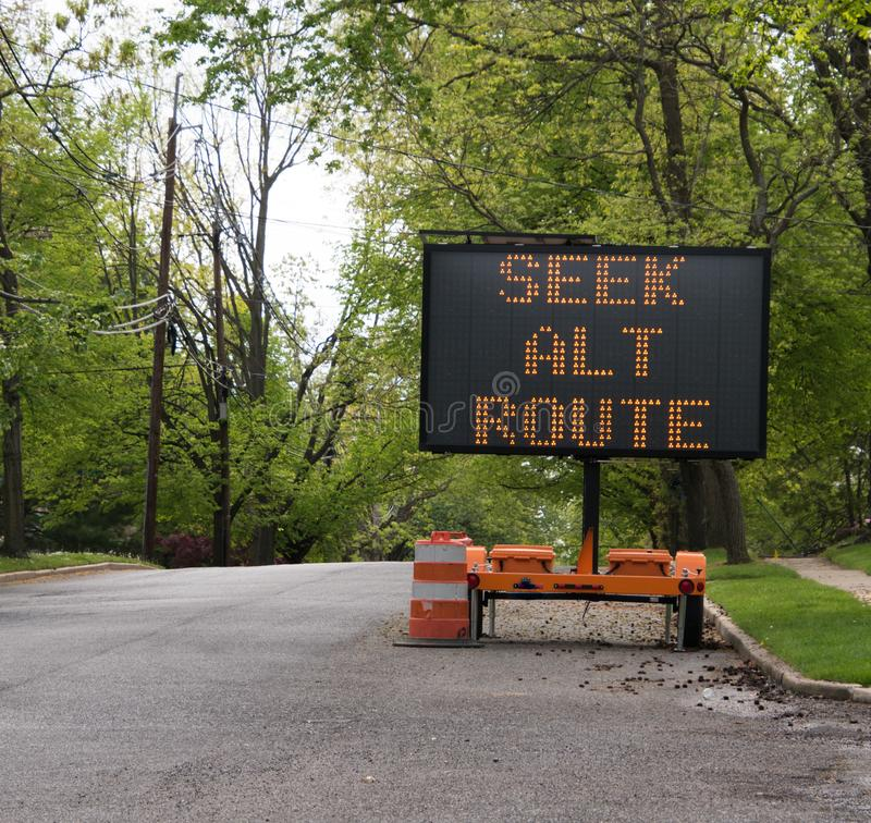 Seek alternate route LED sign on tree lined road. LED road sign on trailer that says, ` seek alternate route` on tree lined suburban street royalty free stock photography