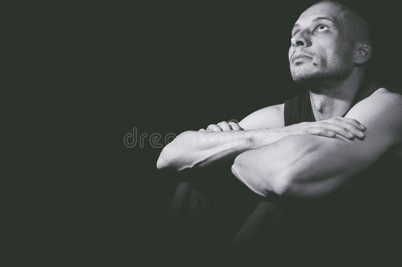 Seeking for God. Young man looking above. Dark image. Black background royalty free stock images