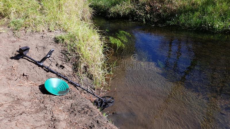 Seeking gold in a river. Seeking gold river panning green detector metal finding precious rare sediment sand water electronics technology scanning outdoors sunny stock photo