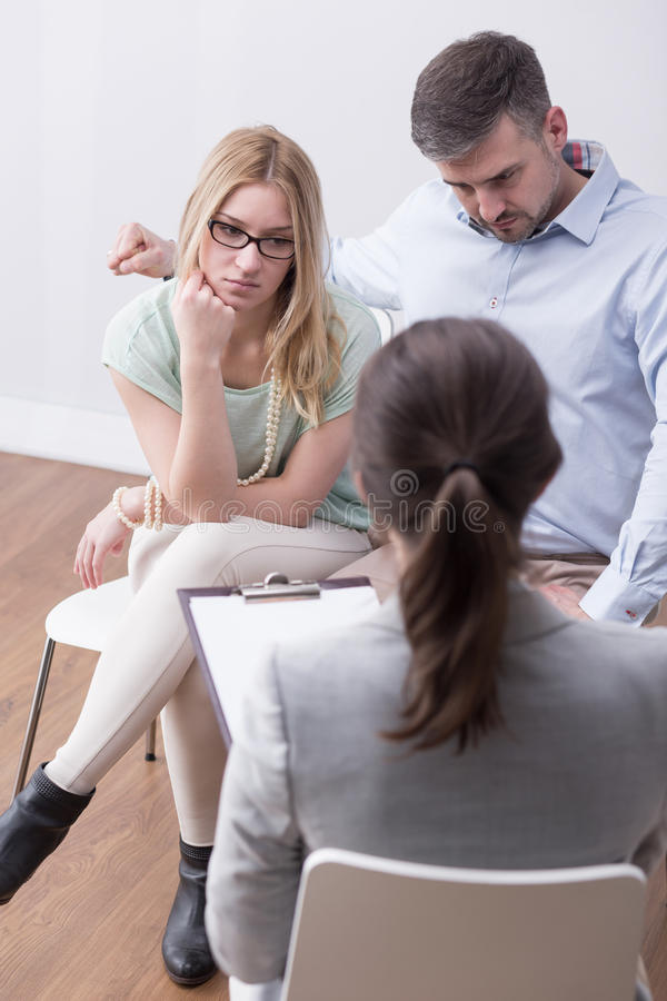 Seeking professional help during times of trouble. Young couple during a family therapy session, sitting in front of a counselor with a flipboard stock images