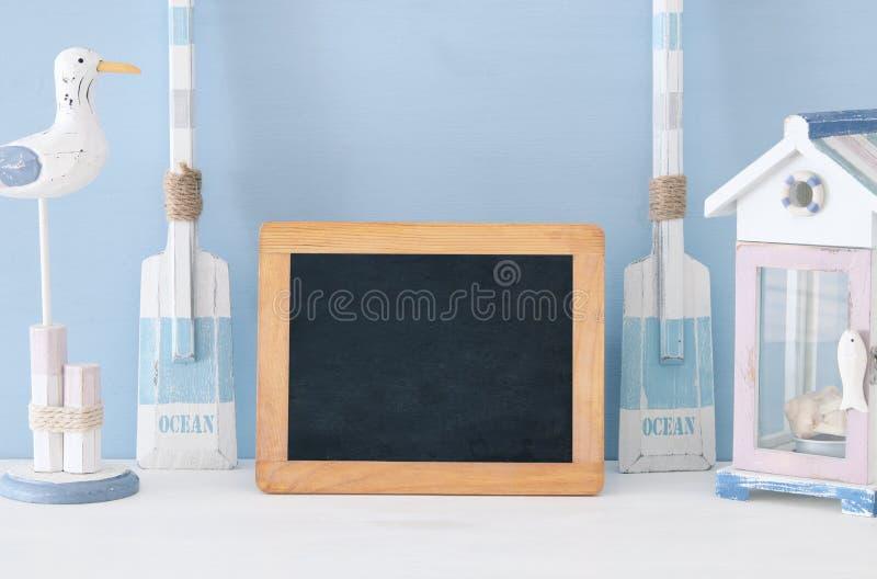 Seekonzept mit weißem dekorativem Seemöwenvogel, Bootsrudern, Strandhaus und leerer Tafel über blauem Hintergrund lizenzfreie stockbilder