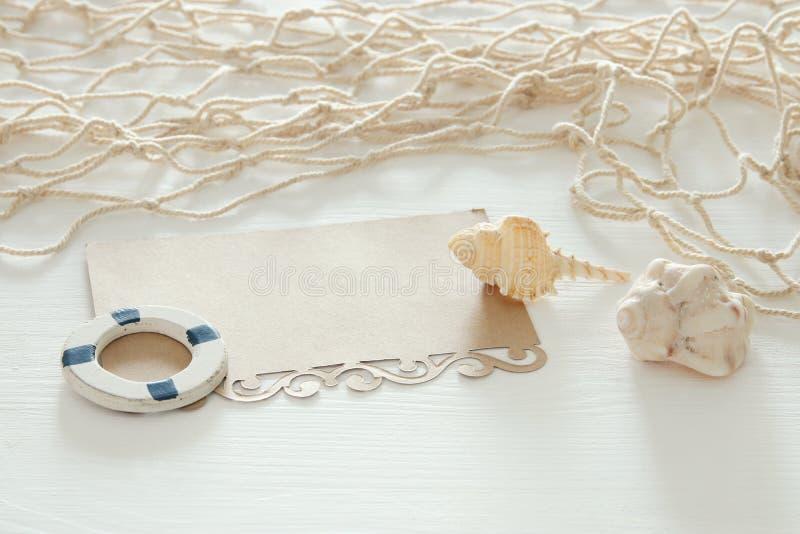 Seekonzeptbild mit Muscheln, Fischnetz und leerer Anmerkung über weißem Holztisch stockbilder