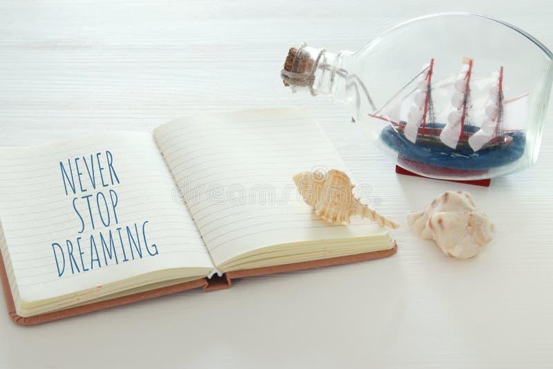 Seekonzeptbild mit Segelboot in der Flasche und in der Anmerkung: HÖREN SIE NIE AUF ZU TRÄUMEN lizenzfreie stockfotografie