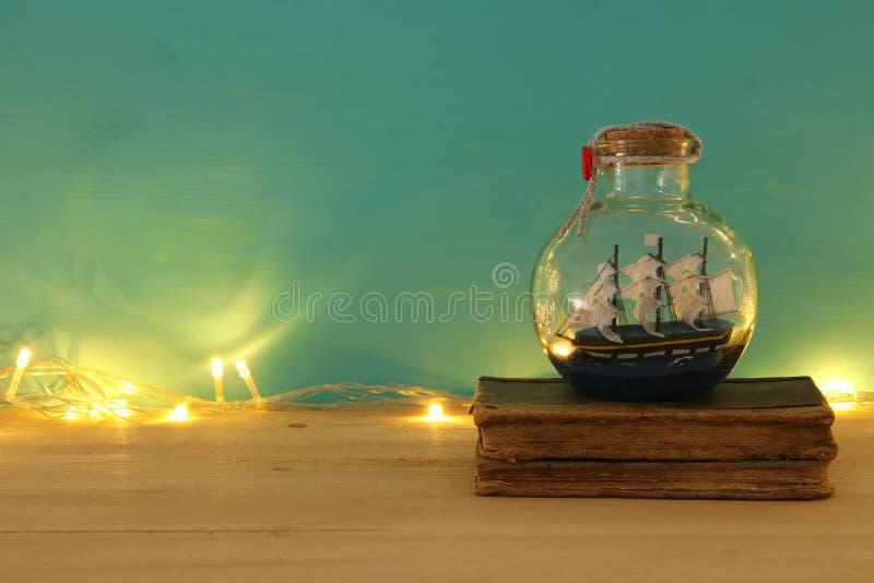 Seekonzeptbild mit Segelboot in der Flasche und in den alten Büchern über Holztisch Selektiver Fokus lizenzfreie stockfotografie