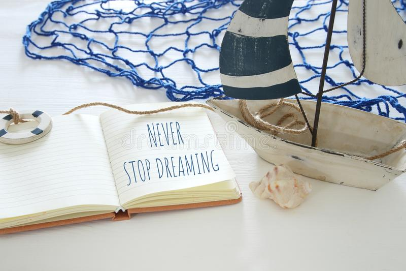 Seekonzeptbild mit weißem dekorativem Segelboot und offenem Notizbuch: HÖREN SIE NIE AUF ZU TRÄUMEN lizenzfreies stockfoto