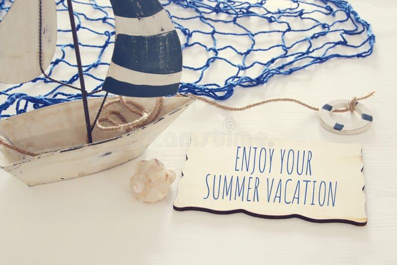 Seekonzeptbild mit weißem dekorativem Segelboot und -text über hölzernem Brett: GENIESSEN SIE IHRE SOMMER-FERIEN stockbild