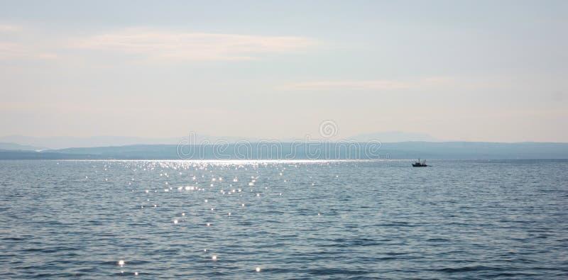 Seelandschaft mit einem Fischerboot an einem sonnigen Sommertag lizenzfreies stockbild